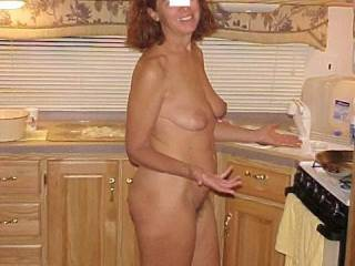 The wife preparing a great meal on a hot day. No need for clothes.